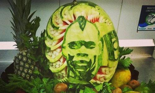 图片中是一盘热带水果,水果中央的西瓜被加以了一番雕刻,巴神的头像